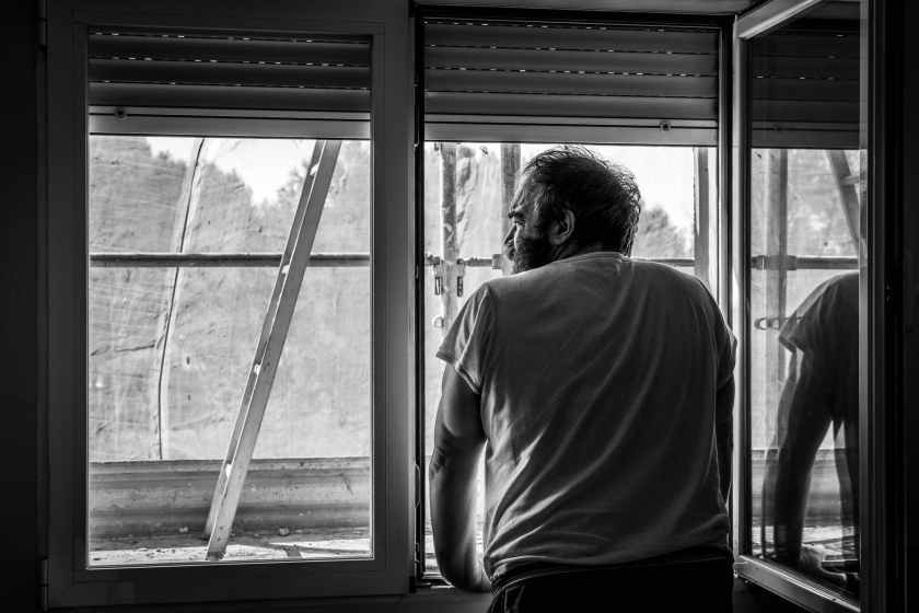man standing beside window