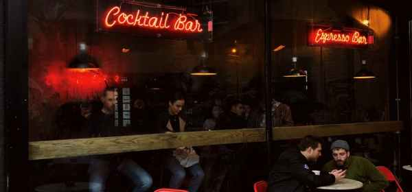 people sitting on chairs in front of red and white unks bar store