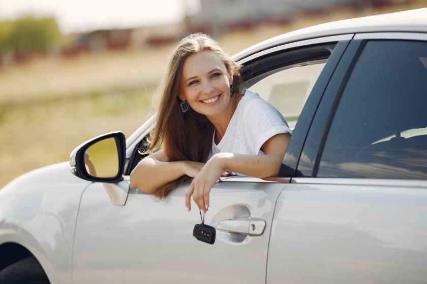 happy woman with car key in modern automobile during car trip
