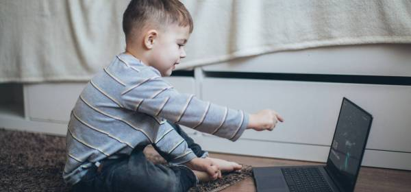 little boy pointing on the laptop