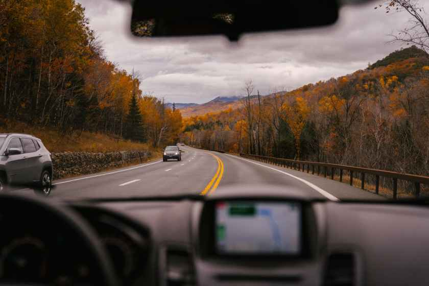 car riding on highway through autumn forest