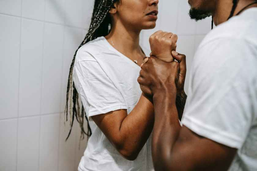 crop anonymous black couple arguing together in bathroom