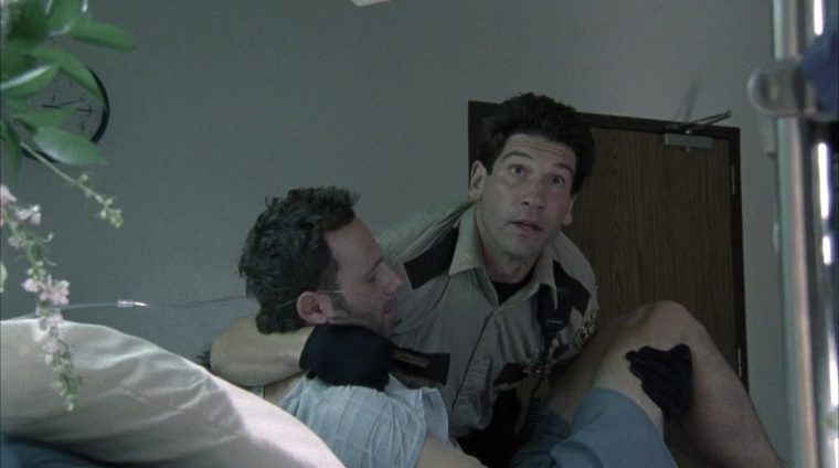 Rick (Lincoln) being carried by Shane (Bernthal) in The Walking Dead (The Walking Dead, AMC)
