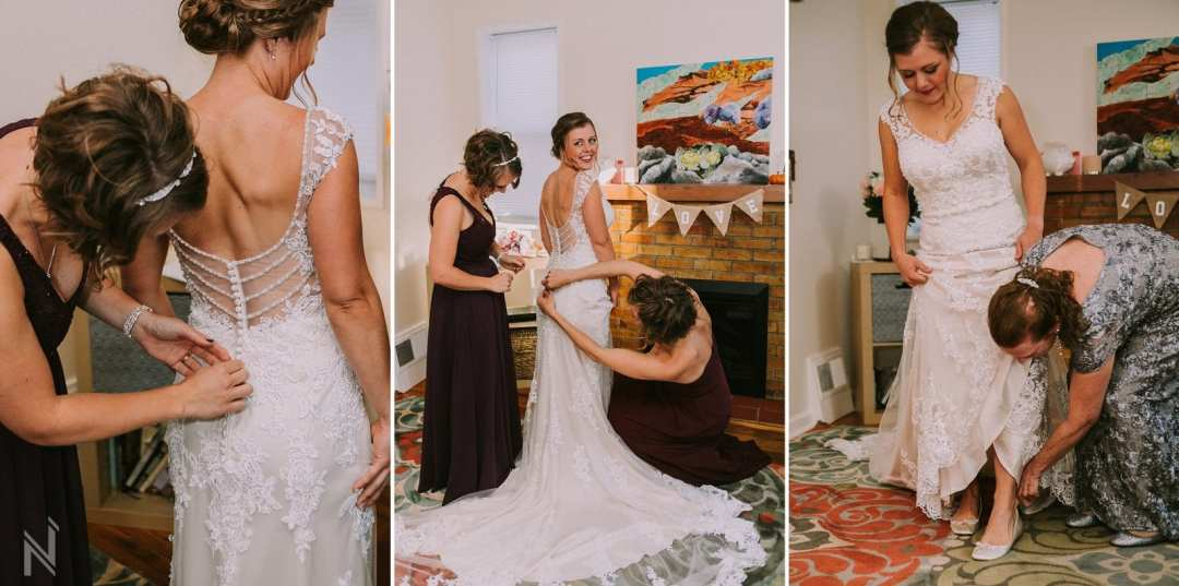 Bride being helped into her lace wedding gown with long train and cap sleeves by her mother and bridesmaids