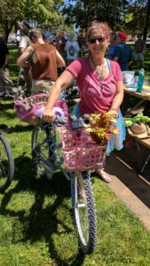 Co-lead bike marshal Ellen with her playa bike ready for action. A woman in a pink shirt with a bike decorated with pink flowers.
