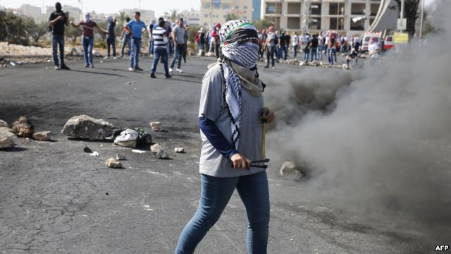 Palestinian protesters hurl stones towards Israeli security forces during clashes near the Beit El settlement on the outskirts of Ramallah in the West Bank, Oct. 17, 2015.