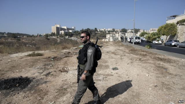 An Israeli border guard walks near the scene where a Palestinian man was killed after he attempted to stab a soldier in the east Jerusalem Jewish settlement of Armon Hanatsiv, adjacent to the Palestinian neighborhood of Jabal Mukaber, Oct. 17, 2015.