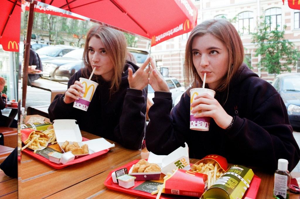 Girl with McDonald's milkshake and meal