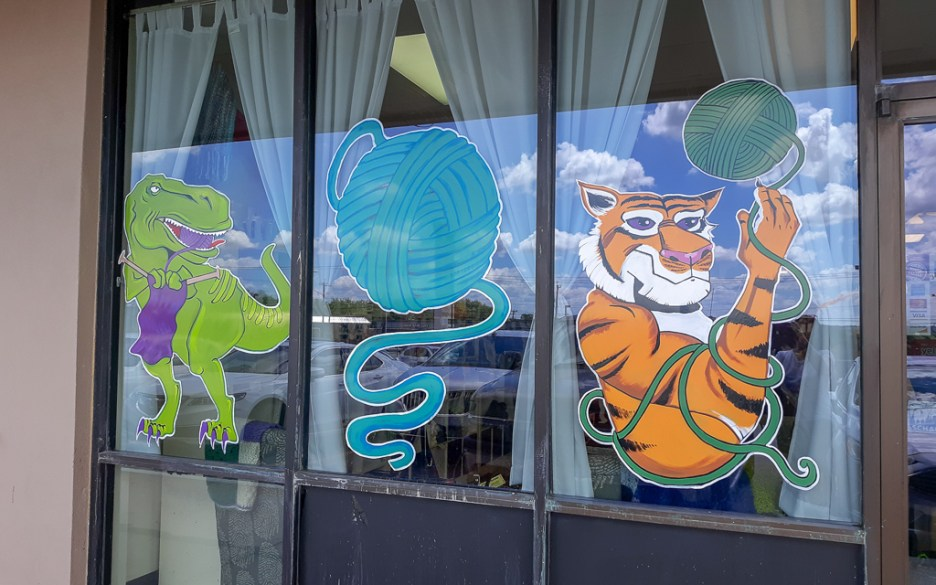 Image of Yarnivore Storefront of a tiger, t-rex, and ball of yarn