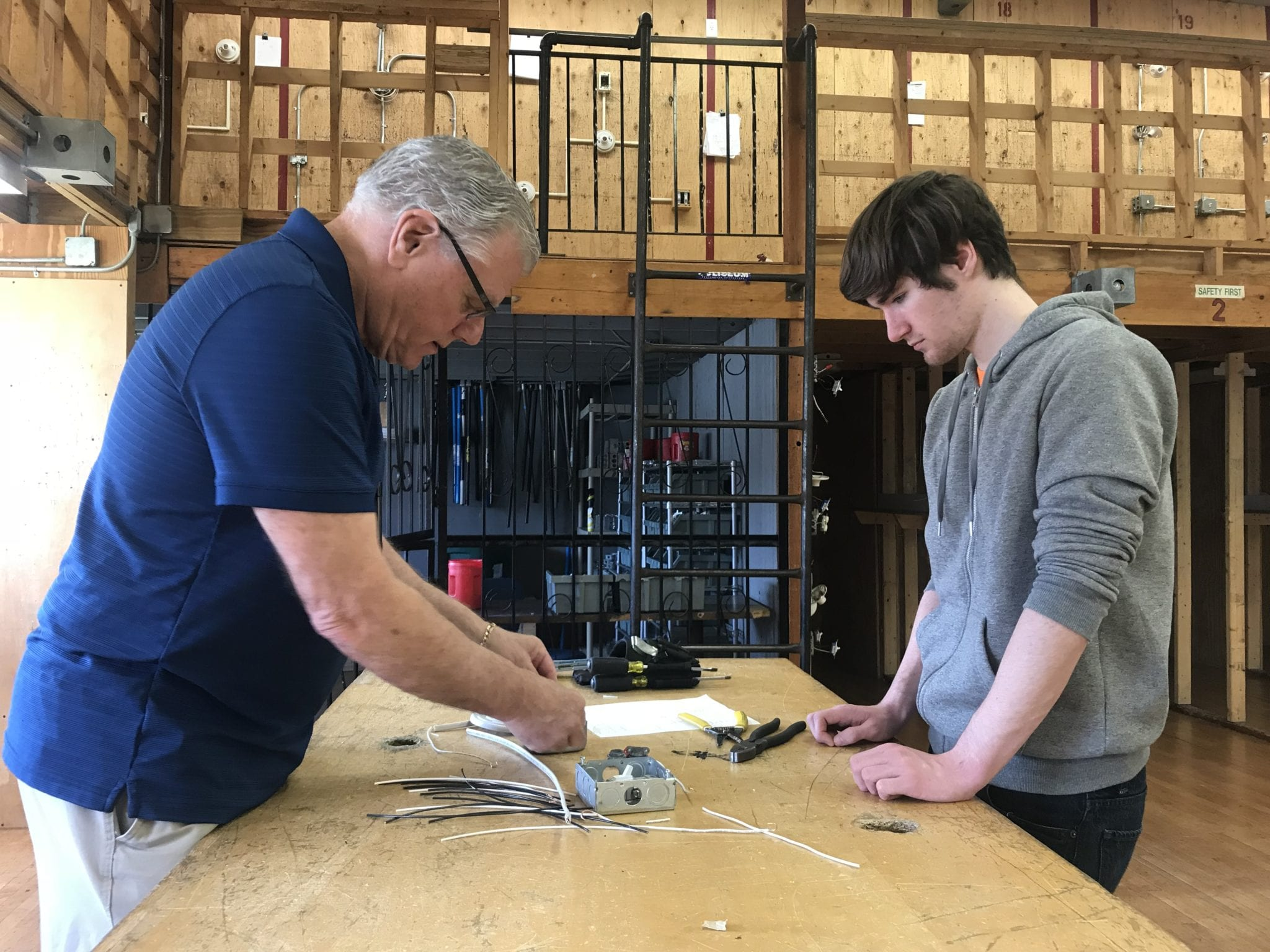 Electrical instructor Frank Barker works with Woburn High School senior Jean Luc Walsh on wiring a power switch. (Courtesy Photo)