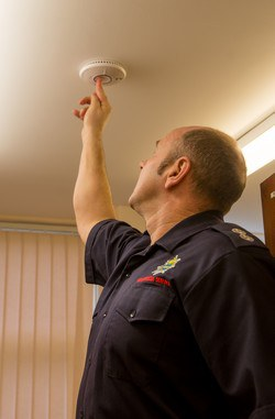 inspector testing a smoke detector