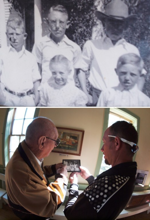 A framed photo on the window sill in the schoolhouse contains a photo of Dale Barnaby with four of his nine brothers and sisters. Here, discussing the photo with his grandson, Mr. Barnaby points himself out in the photo. He's the boy in the middle of the back row.