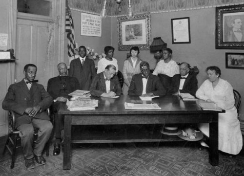 "Group photograph of early NAACP members taken in Dr. Clarence Holme's office in Denver. Caption on back says ""Dr. Holmes Office: Denver. NAACP Meeting? 3rd from Left (Seated) Dr. Westbrook, 2nd from Left (Standing) Mary E Holmes."" (Photo from the Denver Public Library Archive.)"