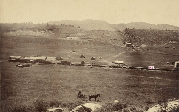 A Greeley, Salt Lake and Pacific Railway train stands on the tracks in this 1893 photo of Stout, Colorado.