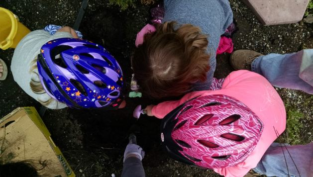Florin and Penny helping their friend plant the new rhubarb in their bike helmets.
