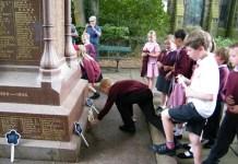 A pupil lays a wooden cross at the War Memorial