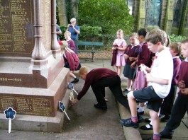 A pupil lays a wooden cross at the War Memorial