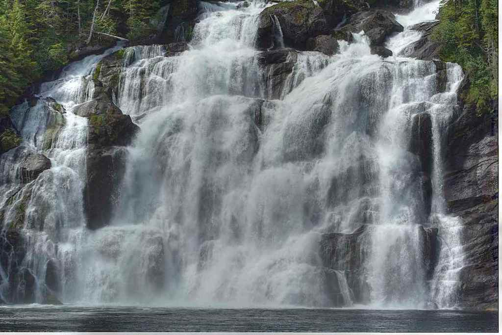 A wide water fall tumbling down a tiered rock face.