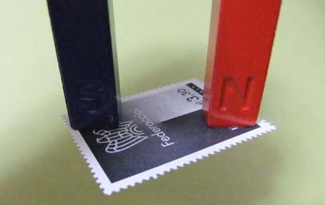 Magnet picking up stamp