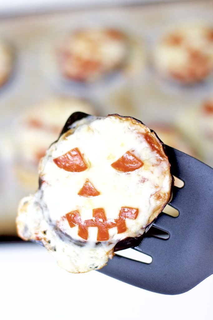 Satisfy all of the ghouls in your life this Halloween when you make these spooky Eggplant Jack-O-Lantern Pizzas for your fright fest. Simple to assemble, and ready in less than 30 minutes, they are perfect for getting the little ones involved as well. Keto Pizza | Ketogenic Diet | Keto Recipes | Halloween Recipe | Kid Friendly | Spooky | Pumpkins | Low Carb | Low Calorie | Gluten-Free Pizza | Scary | Healthy | Fall Recipe | Weight Loss | Easy |