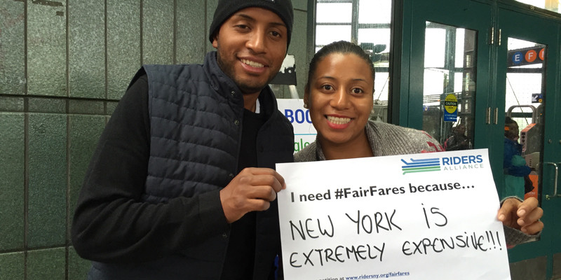 """A man and a woman hold a Riders Alliance sign that says """"I need #FairFares because New York is extremely expensive!!!"""""""