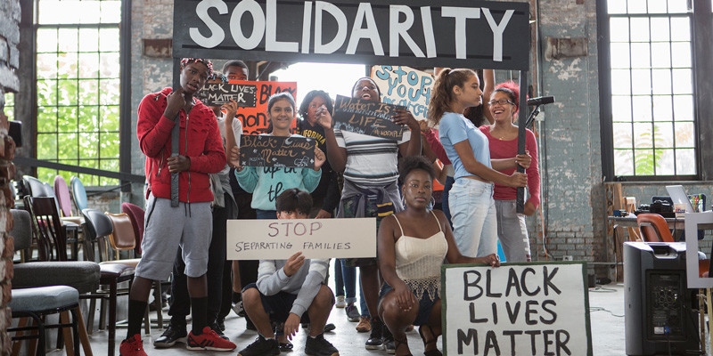 """A diverse group of young people from North Star Fund grantee, Kite's Nest, pose while holding signs with various social justice messages like """"Black Lives Matter"""" and """"Stop Separating Families."""""""