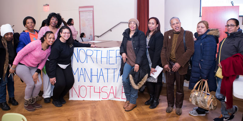 "Ten people with a banner that says ""Northern Manhattan Not for Sale"""