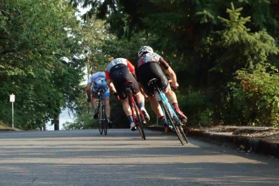 Riders in a breakaway accelerate into the backstretch.