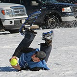 A man with snowshoes on catching a baseball as he falls on the snow covered ground