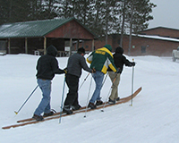 Four people skiing on one pair of giant skis