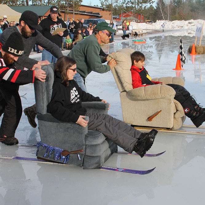Recliners with skis on ice carrying people while being pushed by teammate