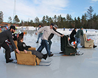 Recliner race with three people sitting on three different recliners which have skis on the bottom of the chairs while two teammates push them on ice