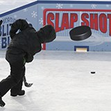 Youth using a hockey stick to slap shot the puck through a slot in a board which is painted with the words slap shot