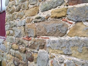 Historic pointing on an old outbuilding where roof tiles were used to fill in larger gaps between the stones, adding to its particular character and appearance. Copyright NYMNPA.