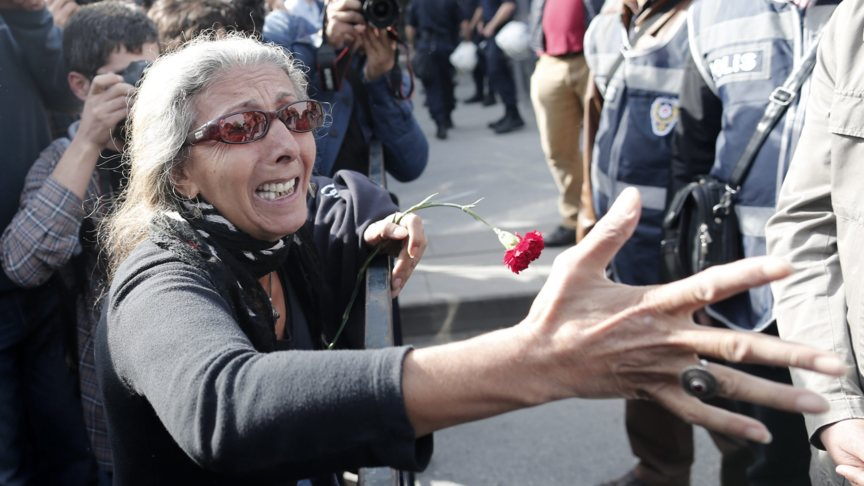 A woman in Ankara, Turkey wants to lay a flower at the place of the terrorist massacre, but police stops her