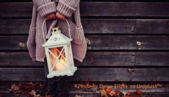Woman holding lantern among autumn leaves