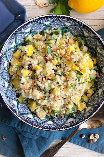 summer squash cauliflower rice salad in a blue bowl