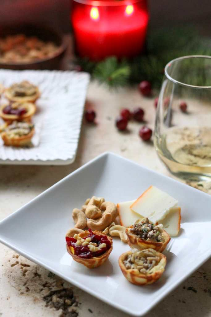 a small white plate with brie bites, cheese, and nuts with a glass of white wine