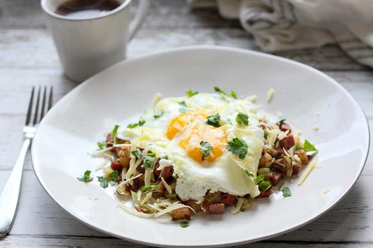 low carb cabbage and corned beef hash on a white plate with a cup of coffee