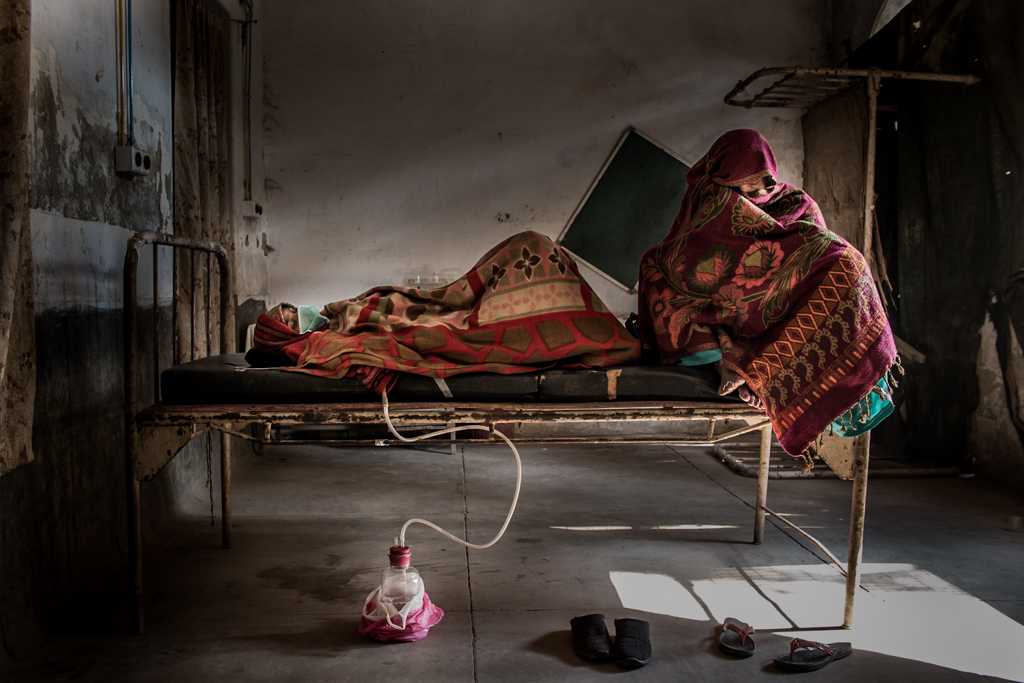 The mother is siting on the old bed while her dauther is sleeping and waiting for the operation.
