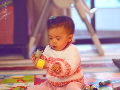 Na imagem: Alice ainda bebê, brincando com chocalhos feitos em casa.