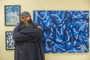 Deuce standing next to his artwork.