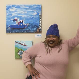 Gwen Johnson (Gigi) standing next to her artwork.
