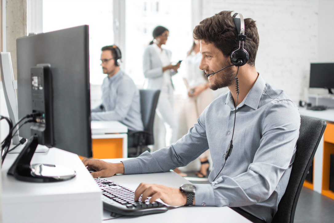 Smiling handsome customer support operator agent with hands-free device working in call center-1