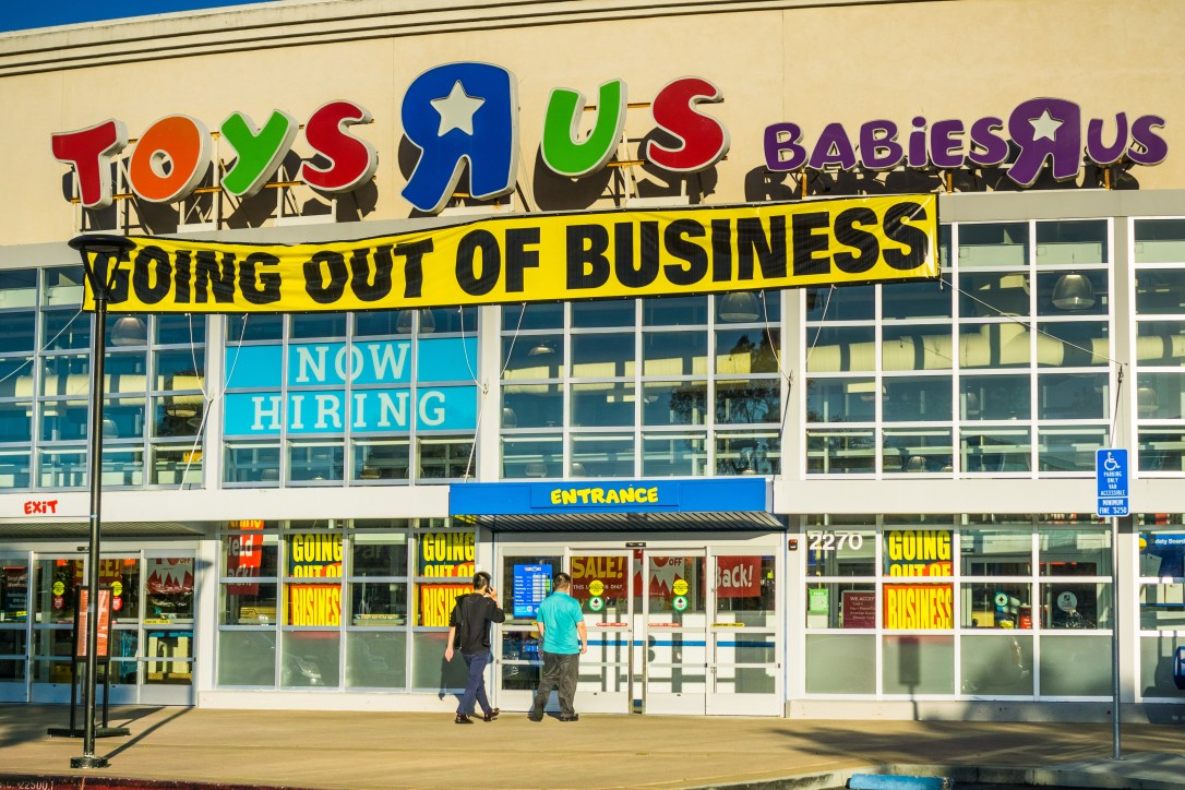 "April 20, 2018 San Mateo / CA / USA - Toys R Us logo and ""Going out of business"" announcement above the entrance to one of the locations in San Francisco bay area; customers going into the store"