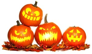 Group of fun lit Halloween Jack o Lanterns with autumn leaves isolated on a white background