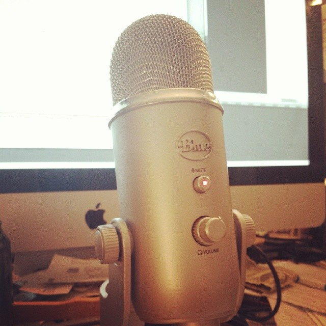 Blue Yeti Microphone on a Desk with Mac behind