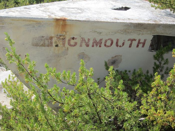 When photographed in March 2011, little identifiable as a boat remained of the wreck above a beach on Cayman Brac. Showing the name Teignmouth and part of the hole where a souvenir hunter has removed Electron.