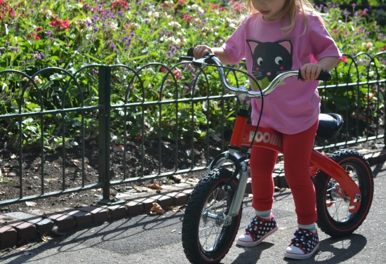 Toddler girl on balance bike in the park