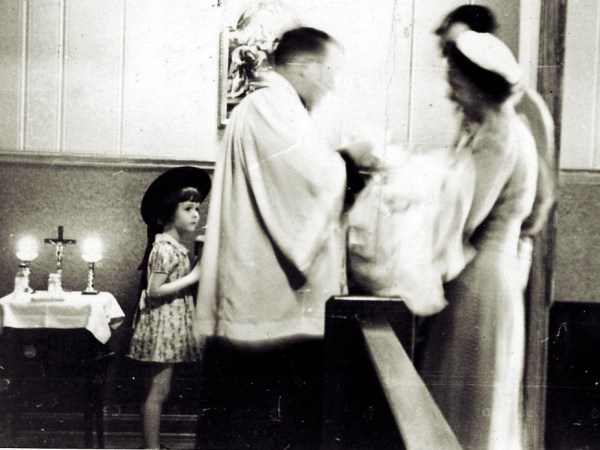Black and white photo, looks to be 1950s or 1960s. In a church, during a baptism. A priest stands facing a mother and father, the mother holds the baby. There is a young girl looking on. The image is blurred where the priest and baby are moving.